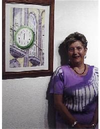 La autora, junto a una acuarela suya sobre el reloj situado en la calle Triana de Las Palmas de Gran Canaria